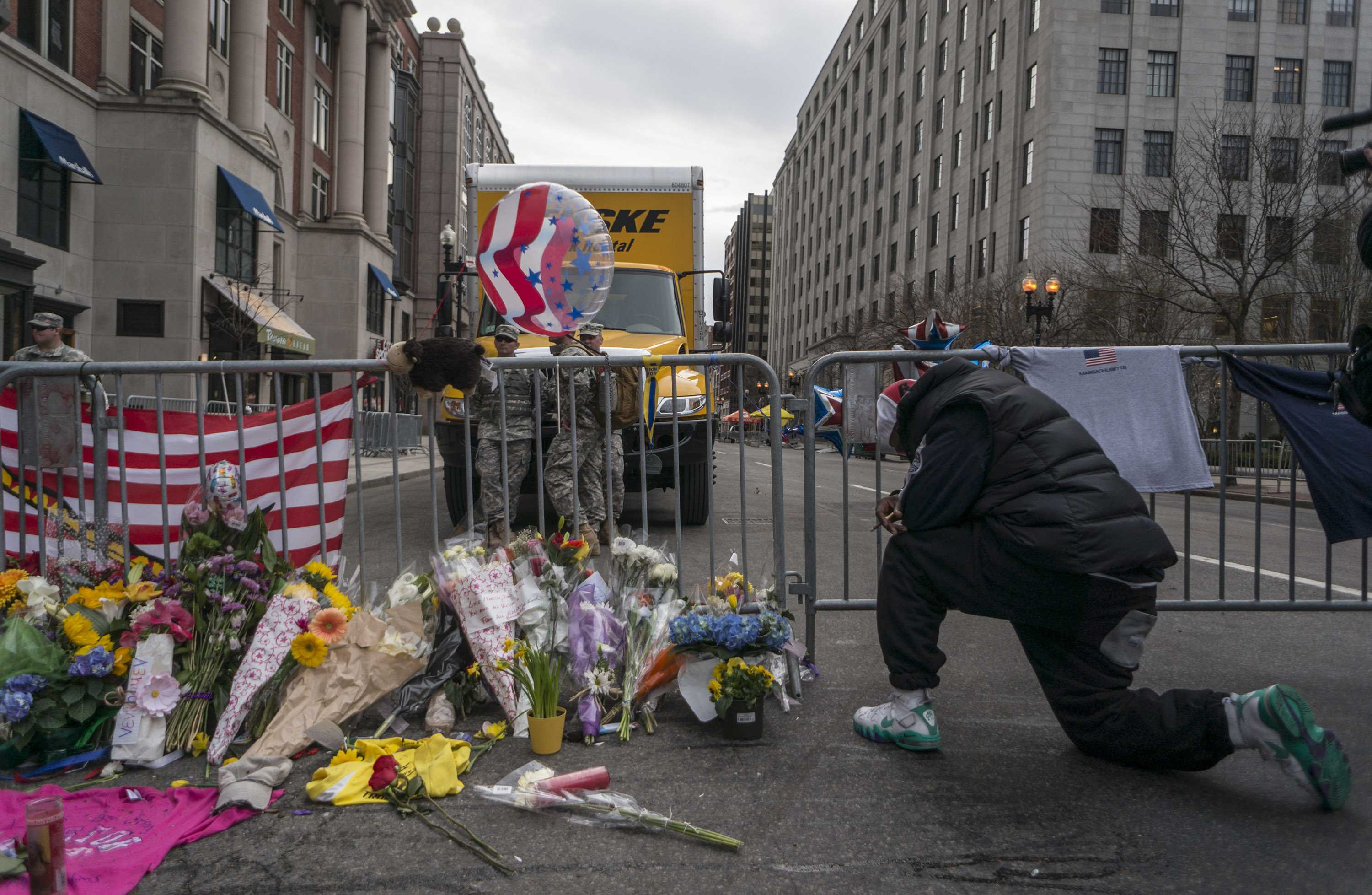 A man knelt by a makeshift memorial built off a police blockade on Boylston Street. Two bombs killed three and injured more than 170 people on Monday near the Boston Marathon finish line. News Staff Photo/Matt Greene