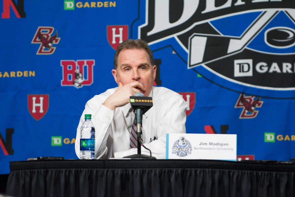 Head Coach Jim Madigan holds his hand to his face during the press conference after Northeaster's loss to Boston University.
