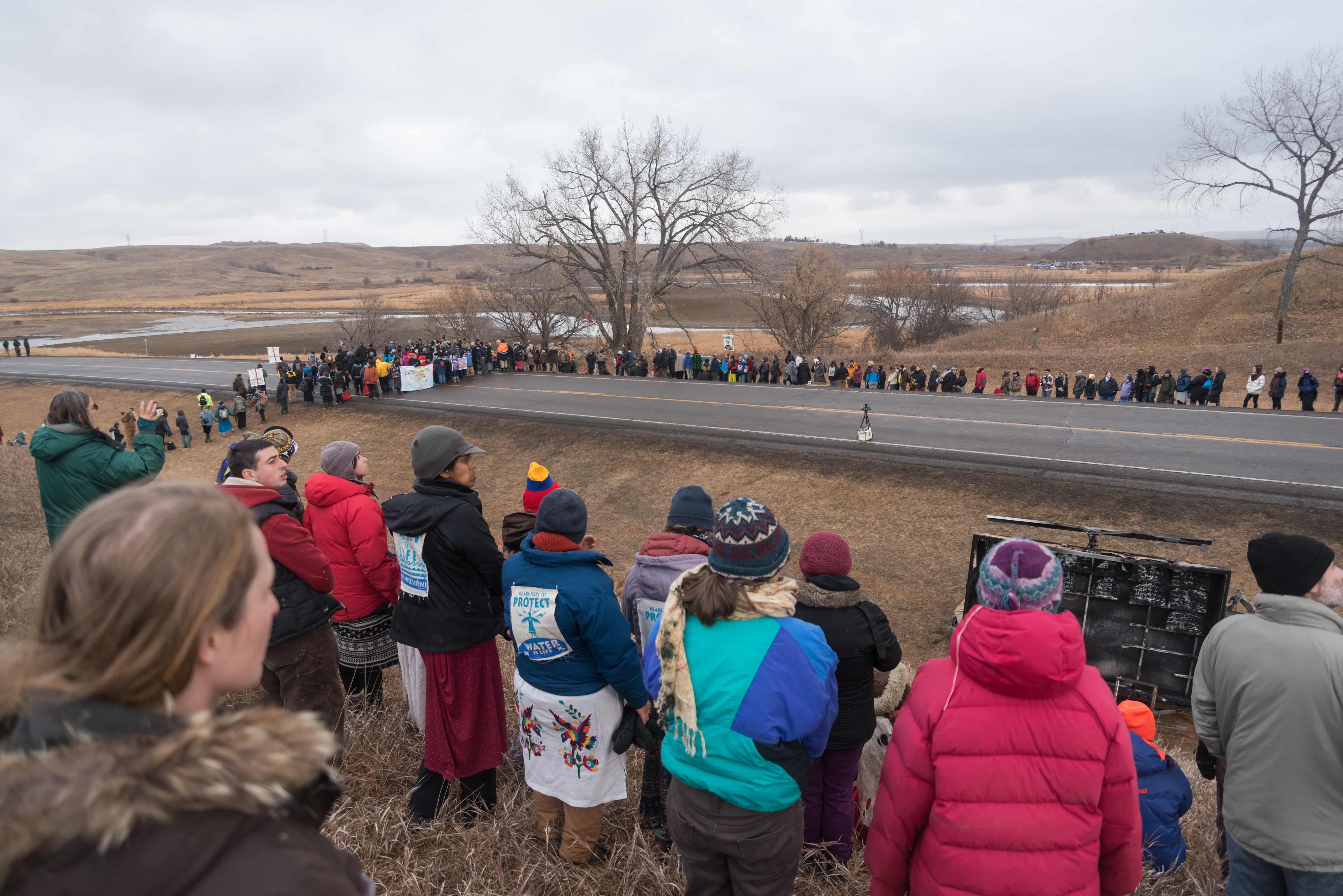 Protesters+to+the+Dakota+Access+Pipeline%2C+self-titled+water+protectors%2C+gather+into+a+circle+before+a+prayer+ceremony+on+Thursday%2C+Nov.+24+near+Backwater+Bridge+in+Cannon+Ball%2C+N.D.+The+bridge+was+closed+and+law+enforcement+added+a+blockade+in+October+after+protesters+set+fire+to+vehicles+on+it.