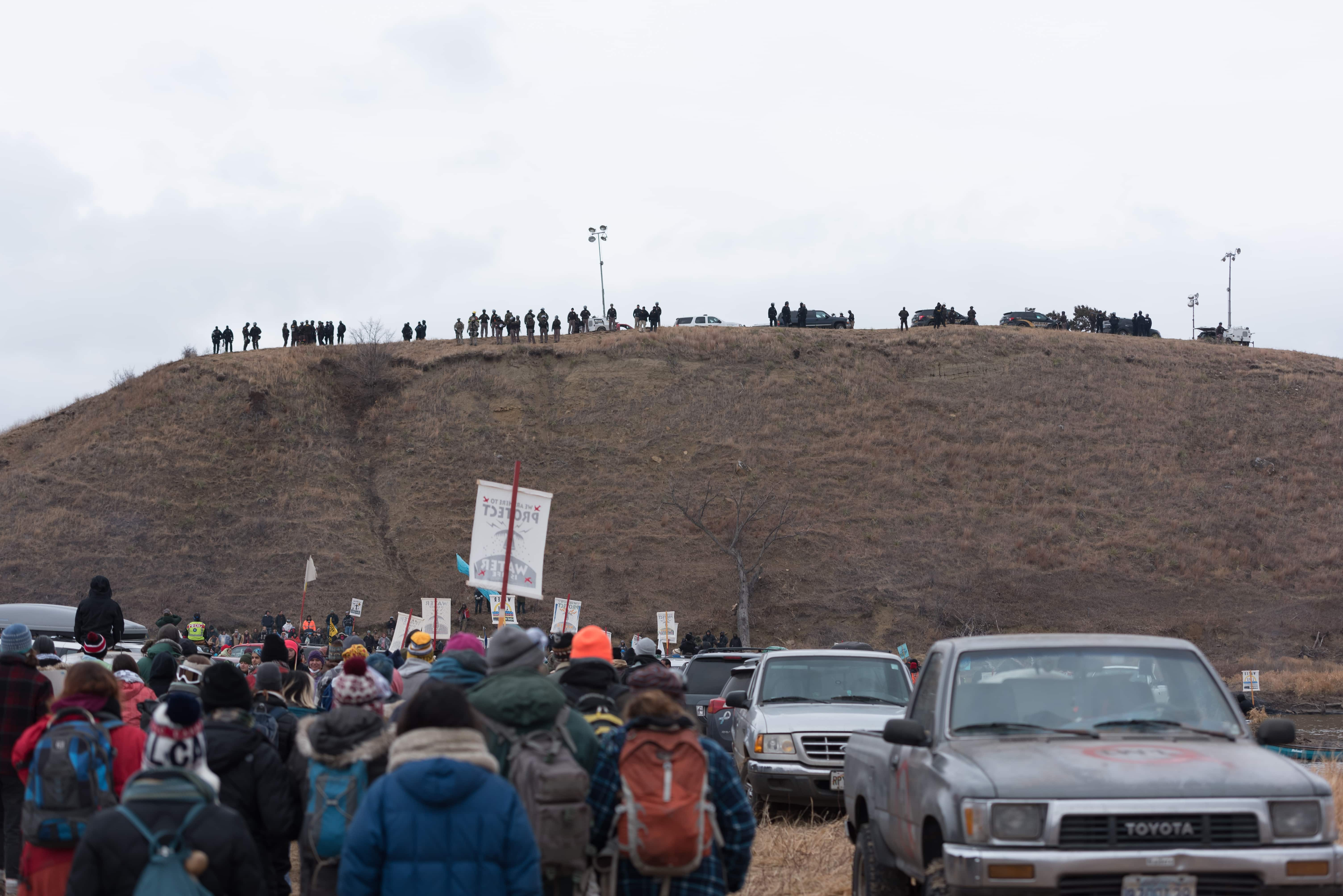 Water+protectors+walk+towards+Turtle+Island+while+Morton+County+Sheriff%E2%80%99s+Department+officers+watch+on+Thursday%2C+Nov.+24.+The+Dakota+Access+Pipeline%2C+a+%243.8+billion+project+proposed+by+Energy+Transfer+Partners+is+supposed+to+run+over+the+alleged+Native+American+burial+site.