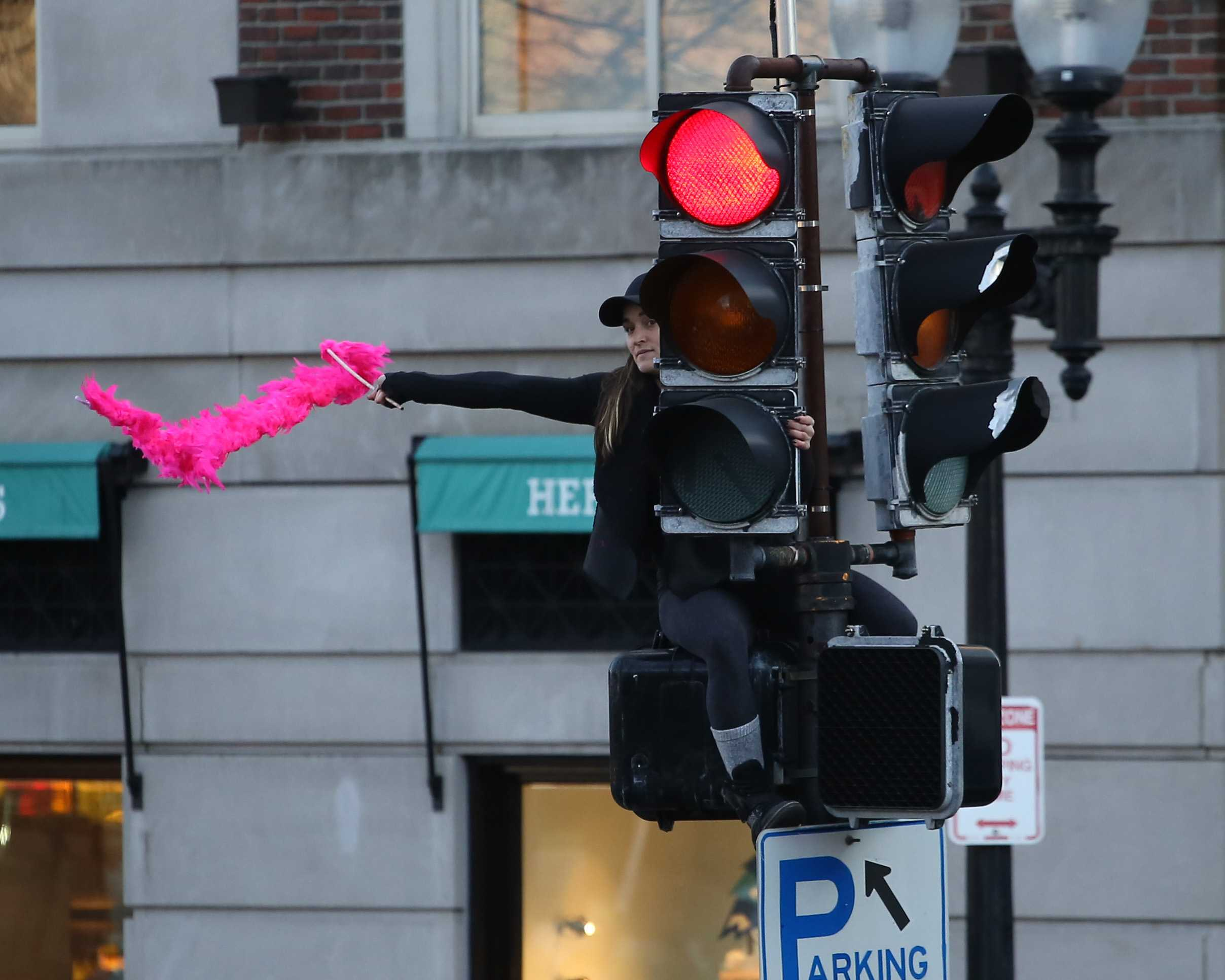 A+member+of+the+march+waves+a+pink+streamer+from+a+traffic+light+post+on+the+corner+of+Boylston+Street+and+Arlington+Street.