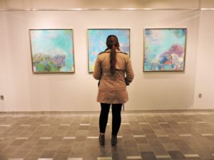 A visitor looks at paintings by Mary Hughes. / Photo by Ashley Wong
