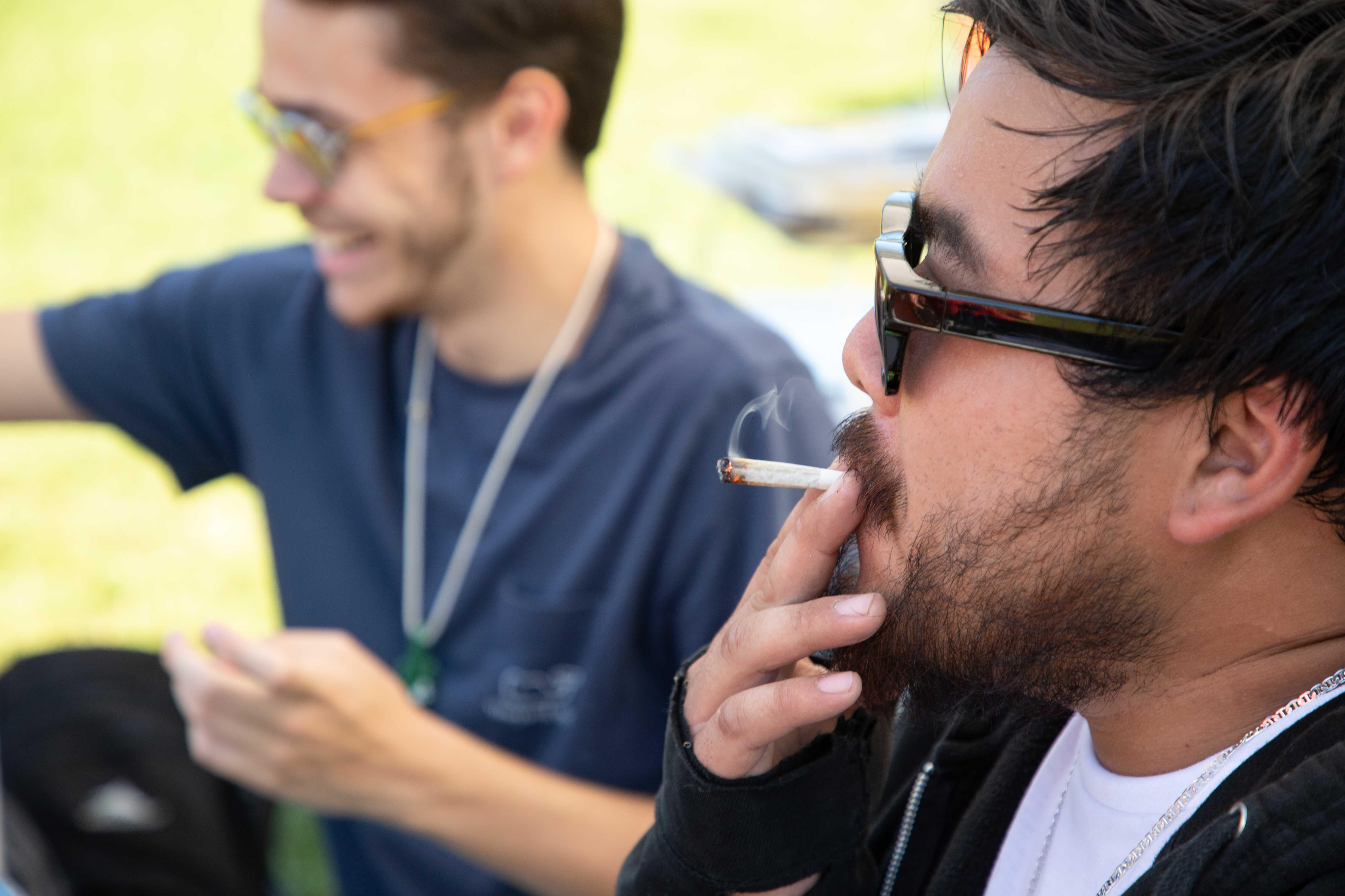 Ashton Chan, at right, of Waltham smokes with Michael Gordon of Framingham Sunday at the Boston Freedom Rally for legalized marijuana Sunday, Sept. 16 on Boston Common. / Photo by Riley Robinson