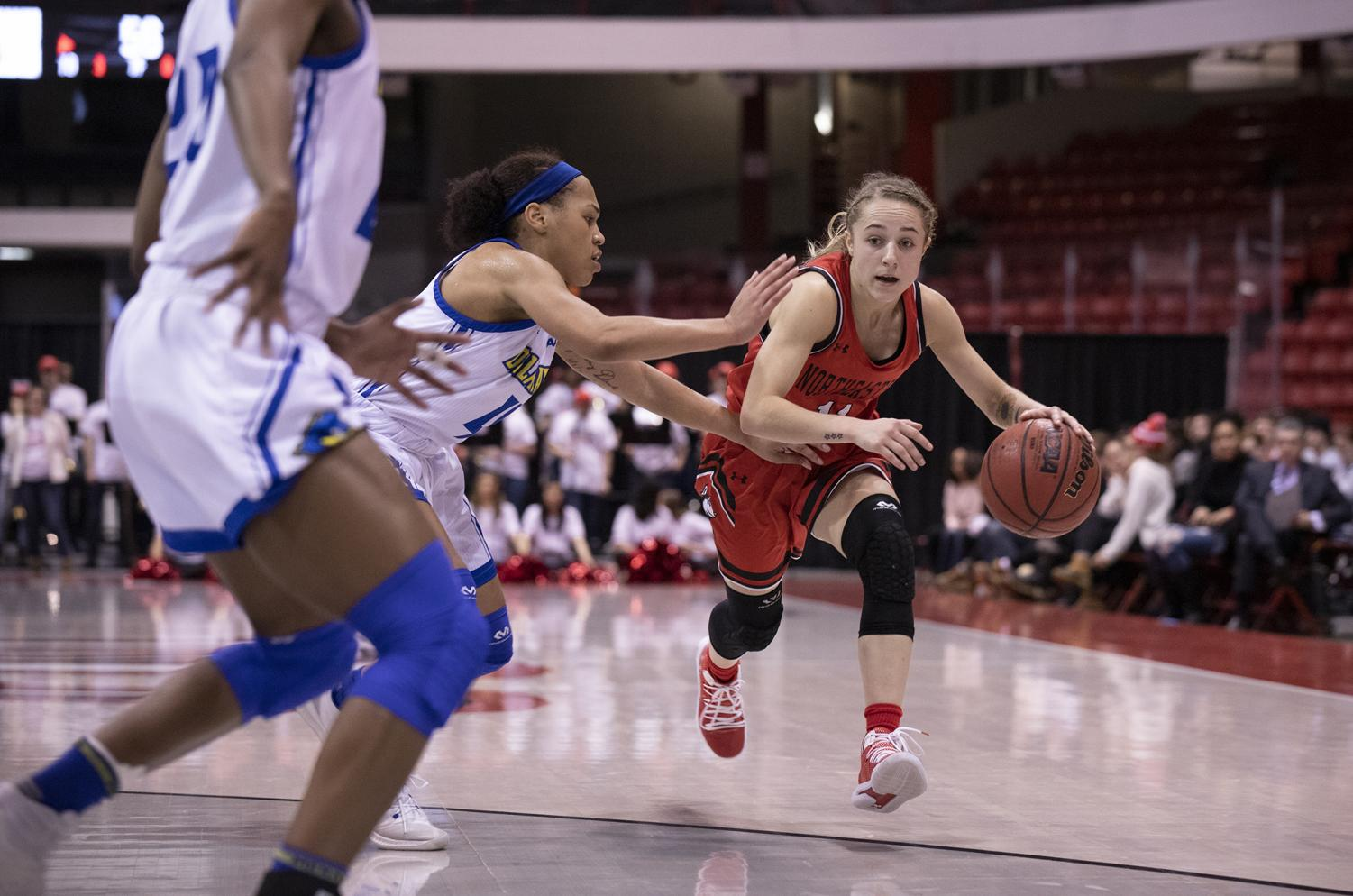 Sophomore guard Stella Clark fends off a University of Delaware defender Saturday, January 20 in Matthews Arena.