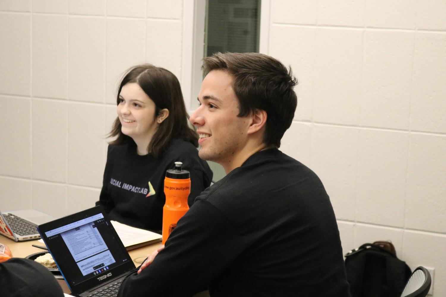 First-year Emerson Toomey (left) and fifth-year Ryan Maia (right) discuss their proposal for the Social Impact-athon.