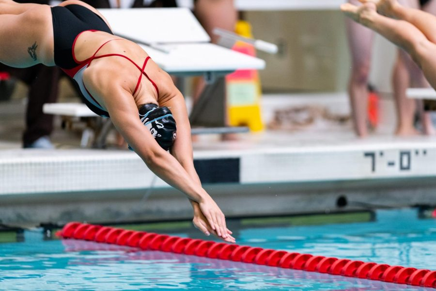 Junior Megan Clark dives into the pool at the start of a race.