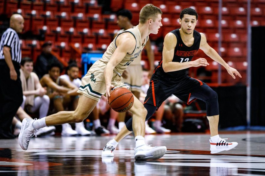 Junior guard Jordan Roland defends against a William and Mary player in a prior game. Roland is in his first year at NU after transferring from George Washington.