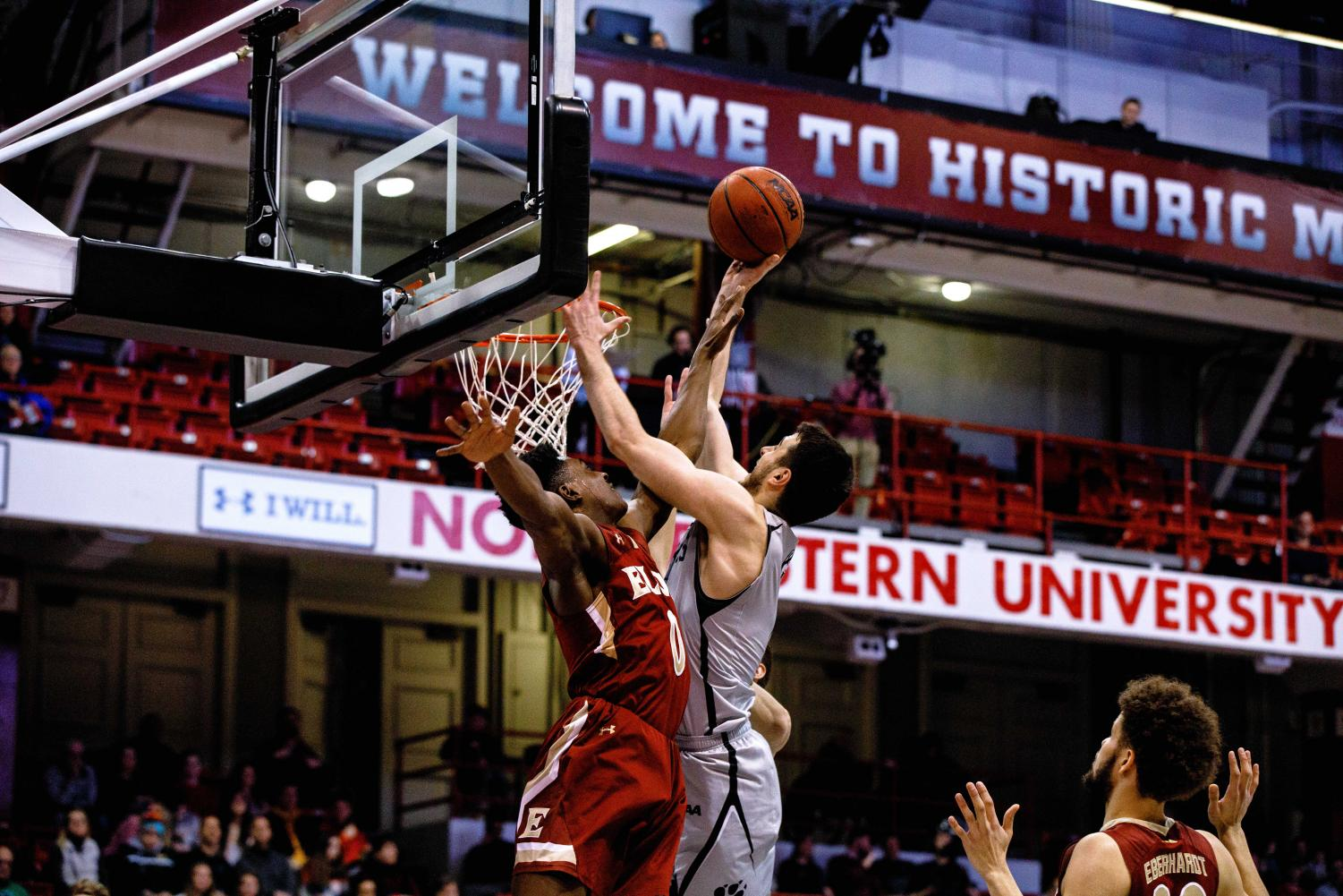 Senior guard Vasa Pusica puts up a shot in traffic in a prior game against Elon. Pusica led the Huskies with 19 points Thursday.