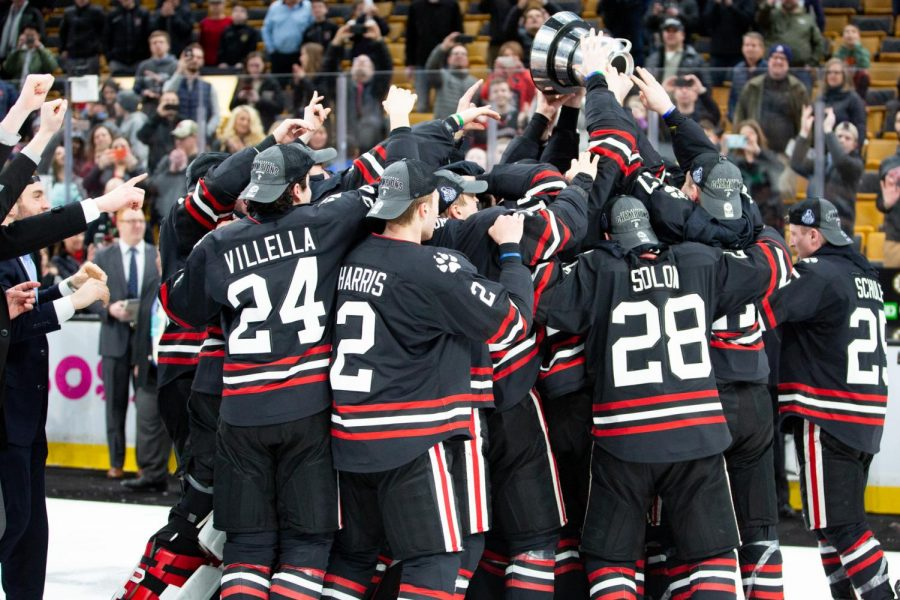 The+Huskies+crowd+around+captain+Eric+Williams+as+he+lifts+the+Beanpot+trophy+after+NU+beat+BC%2C+4-2+at+TD+Garden+Monday+night.