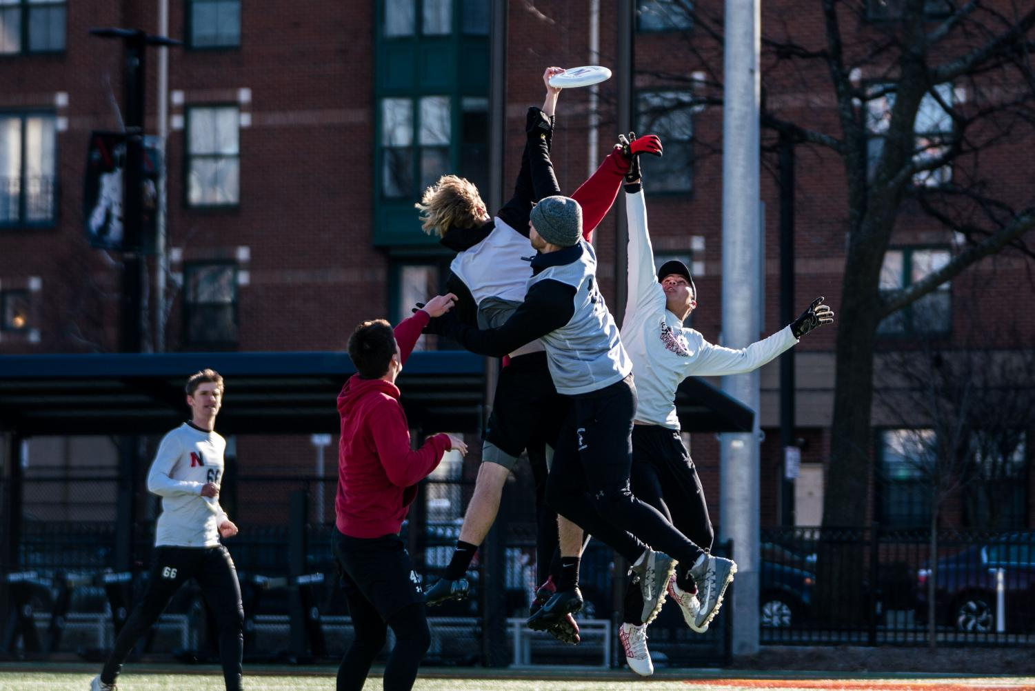 Multiple members of the club ultimate Frisbee team leap for the disc during a practice Feb. 16.