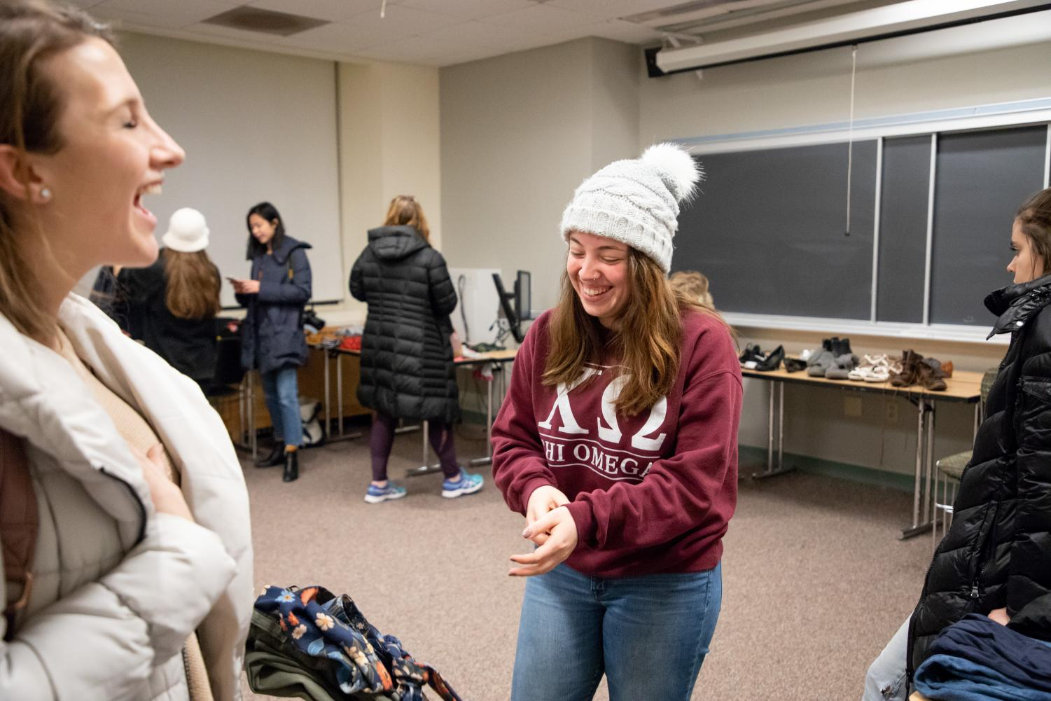Director of Trash2Treasure marketing Jackie Arce, a 4th year design major, laughs with participants at the clothing exchange.