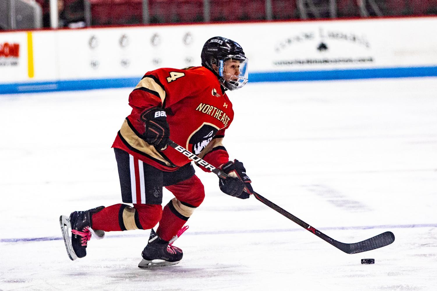 Junior defender Codie Cross moves the puck up the ice in a prior game against Vermont. Cross scored three points Friday on a goal and two assists.