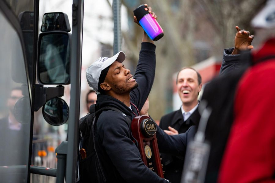 Junior guard Shawn Occeus exits the team bus with the CAA Tournament trophy in hand March 13.