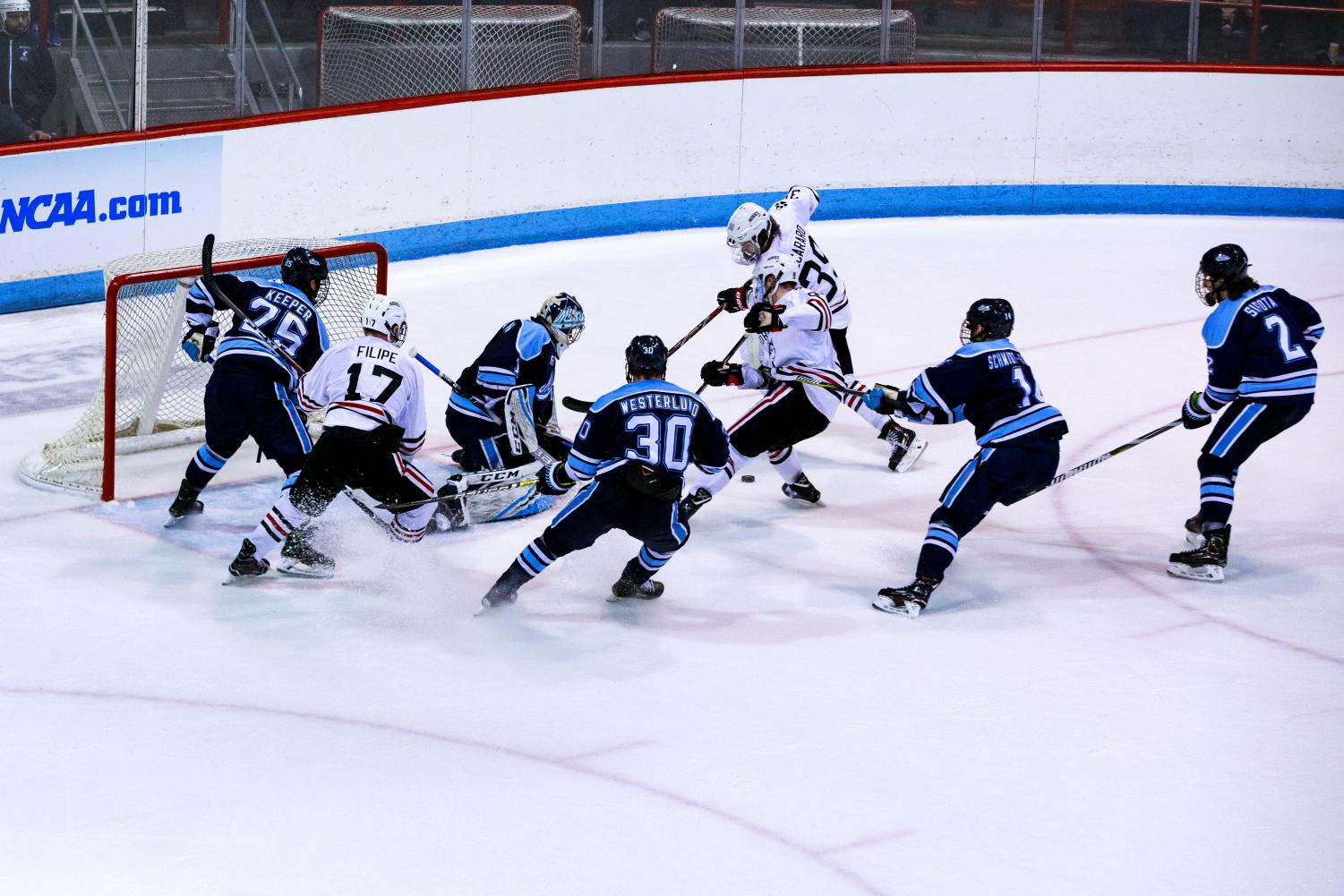 NU forwards Tyler Madden (9) and Liam Pecararo (39) scramble for a loose puck in front of the Maine net.