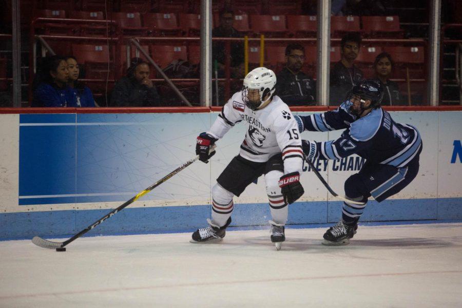 Junior winger Grant Jozefek fends off Maine junior center Tim Doherty.