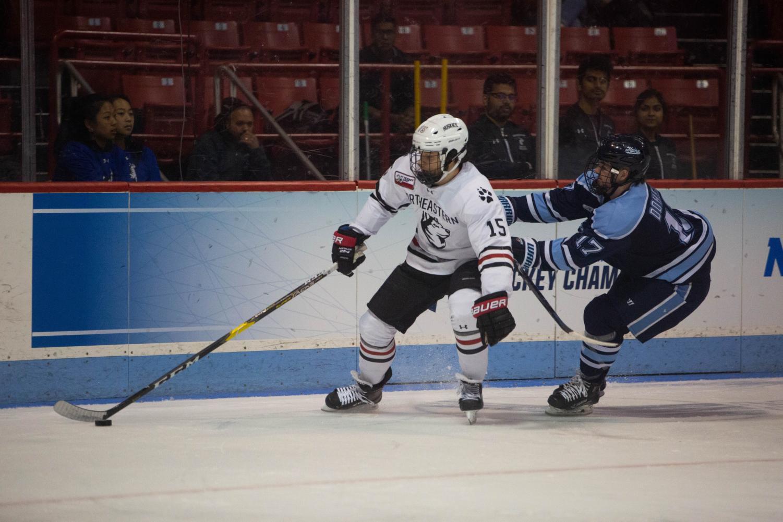 Junior winger Grant Jozefek fends off Maine center Tim Doherty at Matthews Arena last season.