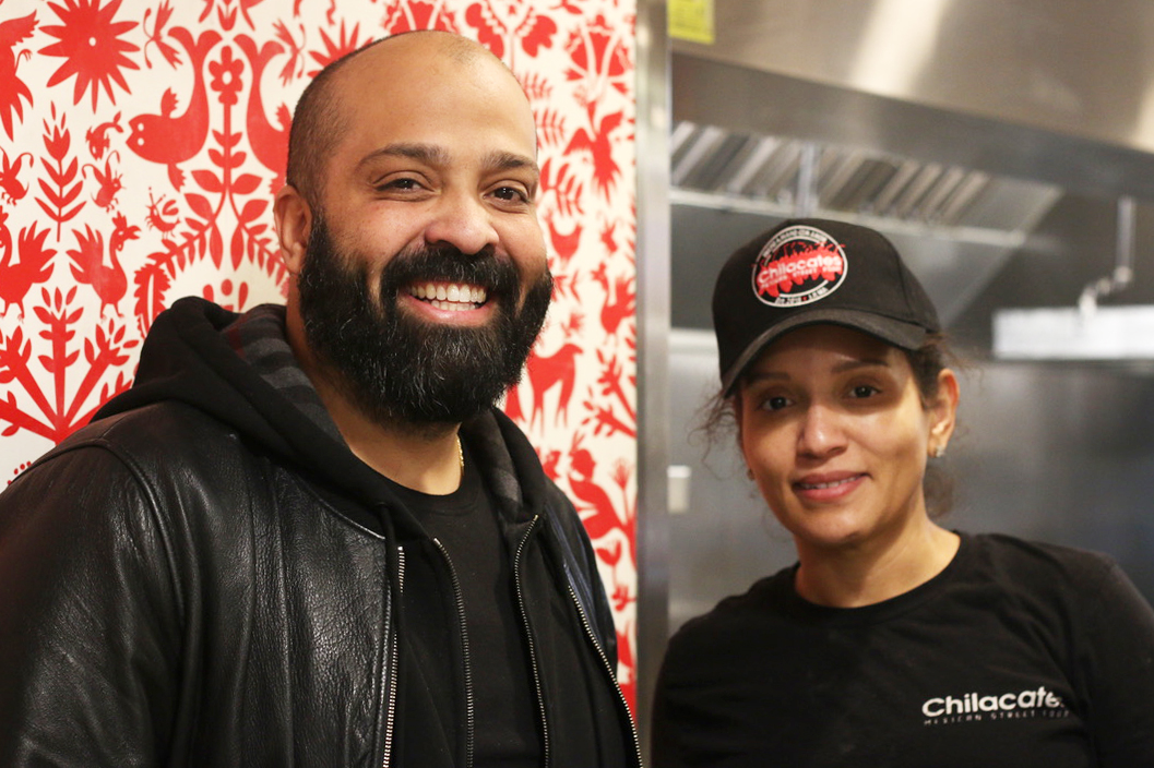 Socrates Abreu, who started the Jamaica Plain based Chilacates stands next to his sister-in-law Kaurys Lajara, who runs one of the store's newest branches in Mission Hill.