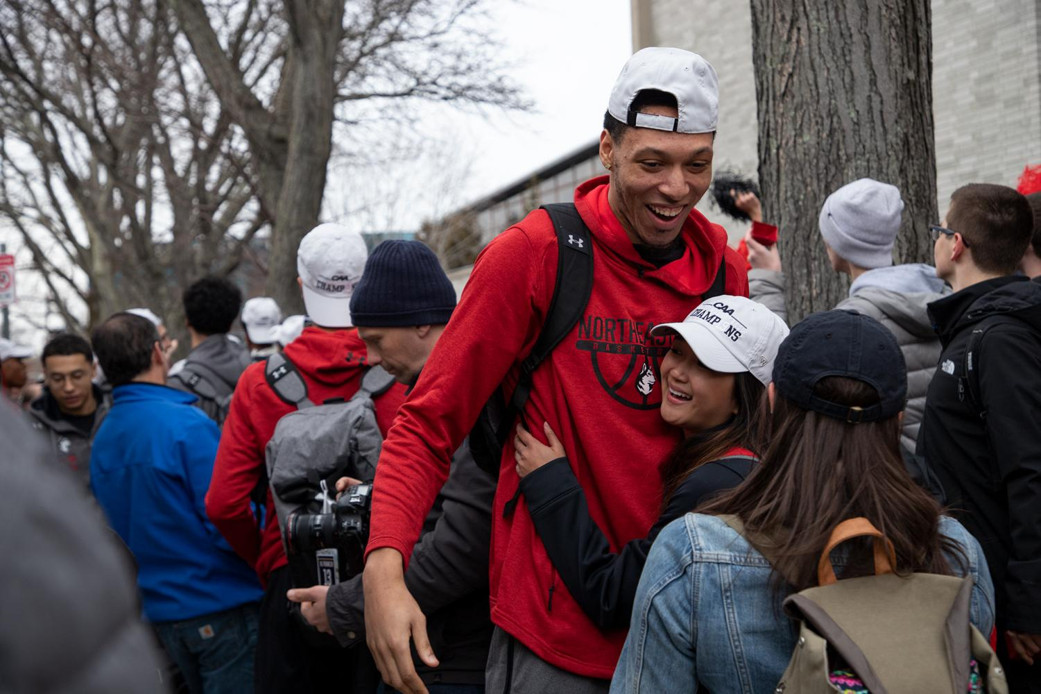 Senior+forward+Jeremy+Miller+receives+a+hug+from+fifth-year+dance+team+member+Chelsea+Pe+Benito+upon+returning+to+campus.