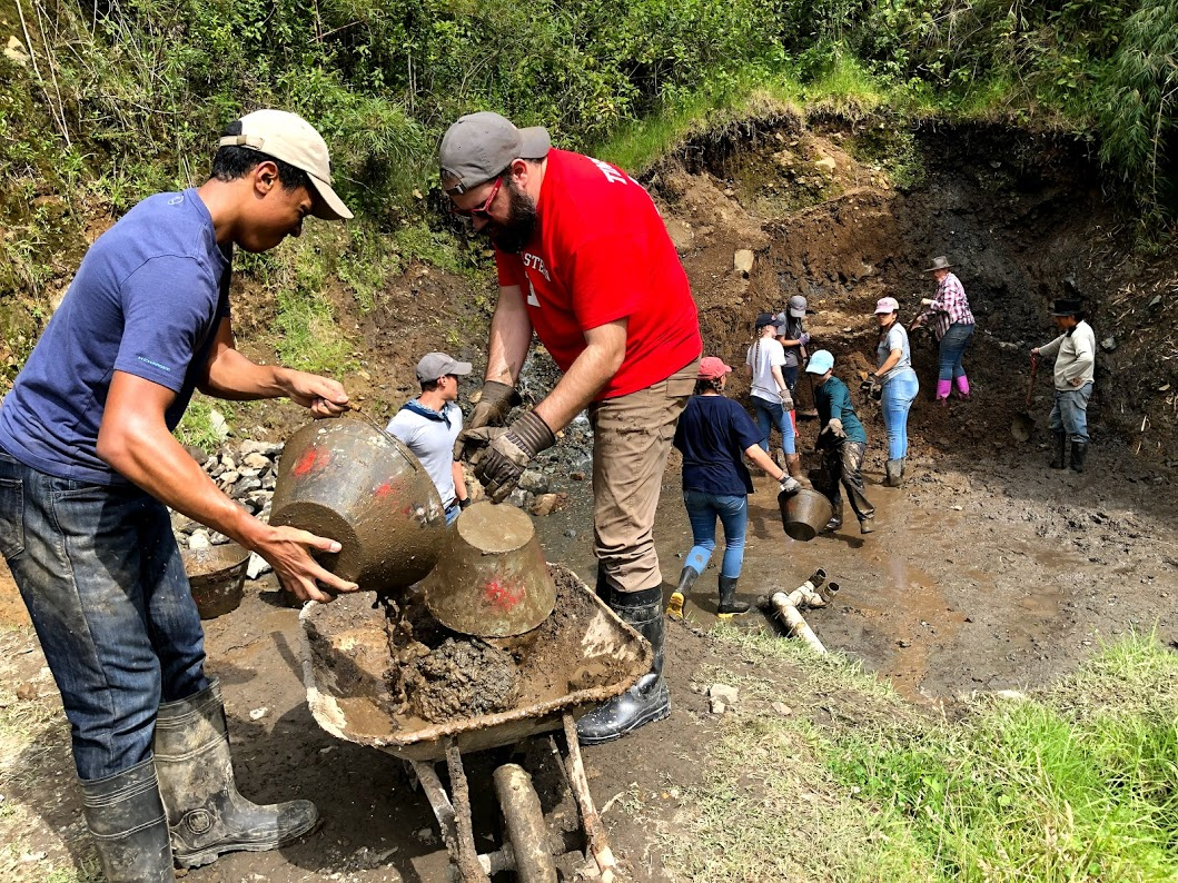 Student volunteers in Ecuador help dig out a pool in order to fit a water tank.