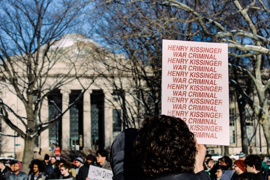 A+protester+holds+up+a+sign+opposing+former+U.S.+Secretary+of+State+Henry+Kissinger+at+an+event+celebrating+MIT%27s+new+Stephen+A.+Schwarzman+College+of+Computing.+