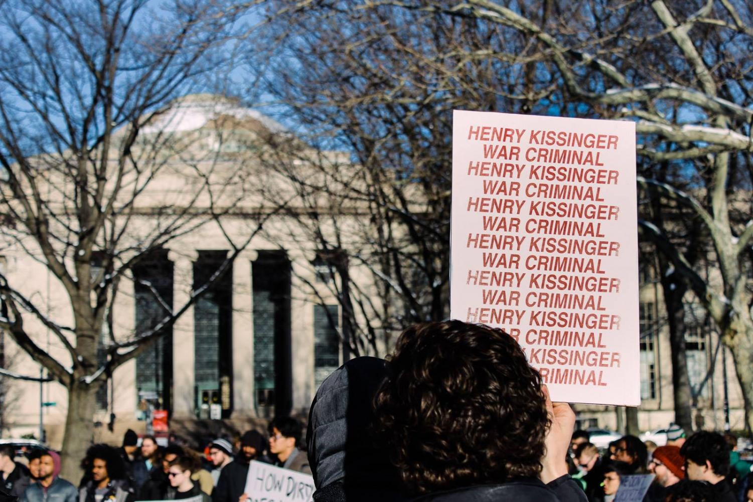 A protester holds up a sign opposing former U.S. Secretary of State Henry Kissinger at an event celebrating MIT's new Stephen A. Schwarzman College of Computing.