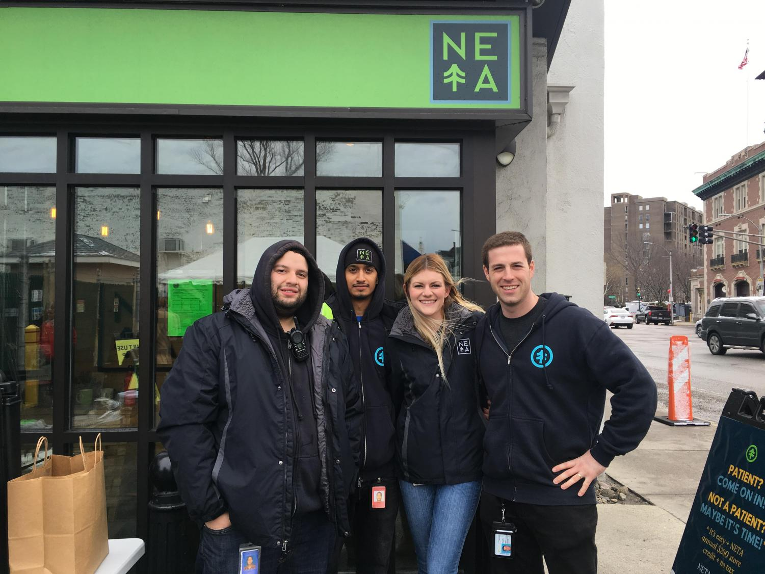 NETA employees stand outside the company's Brookline location, which opened its doors to recreational users Saturday.