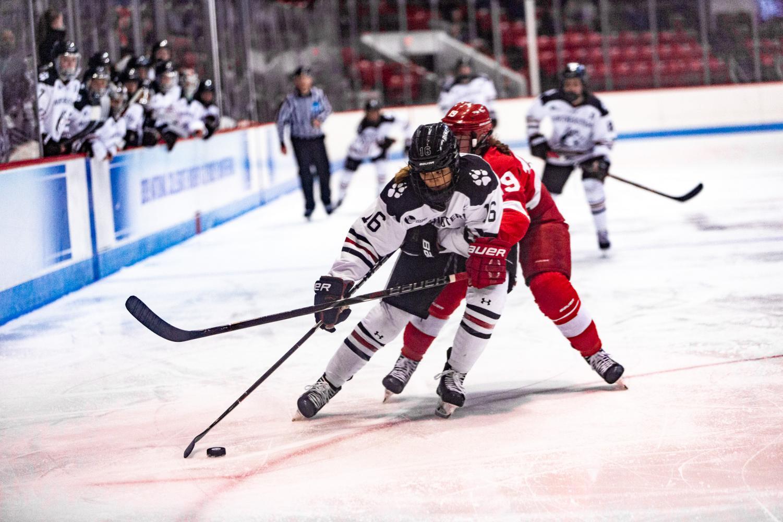 Junior forward Matti Hartman tries to power her way around a Cornell defender in the offensive zone.