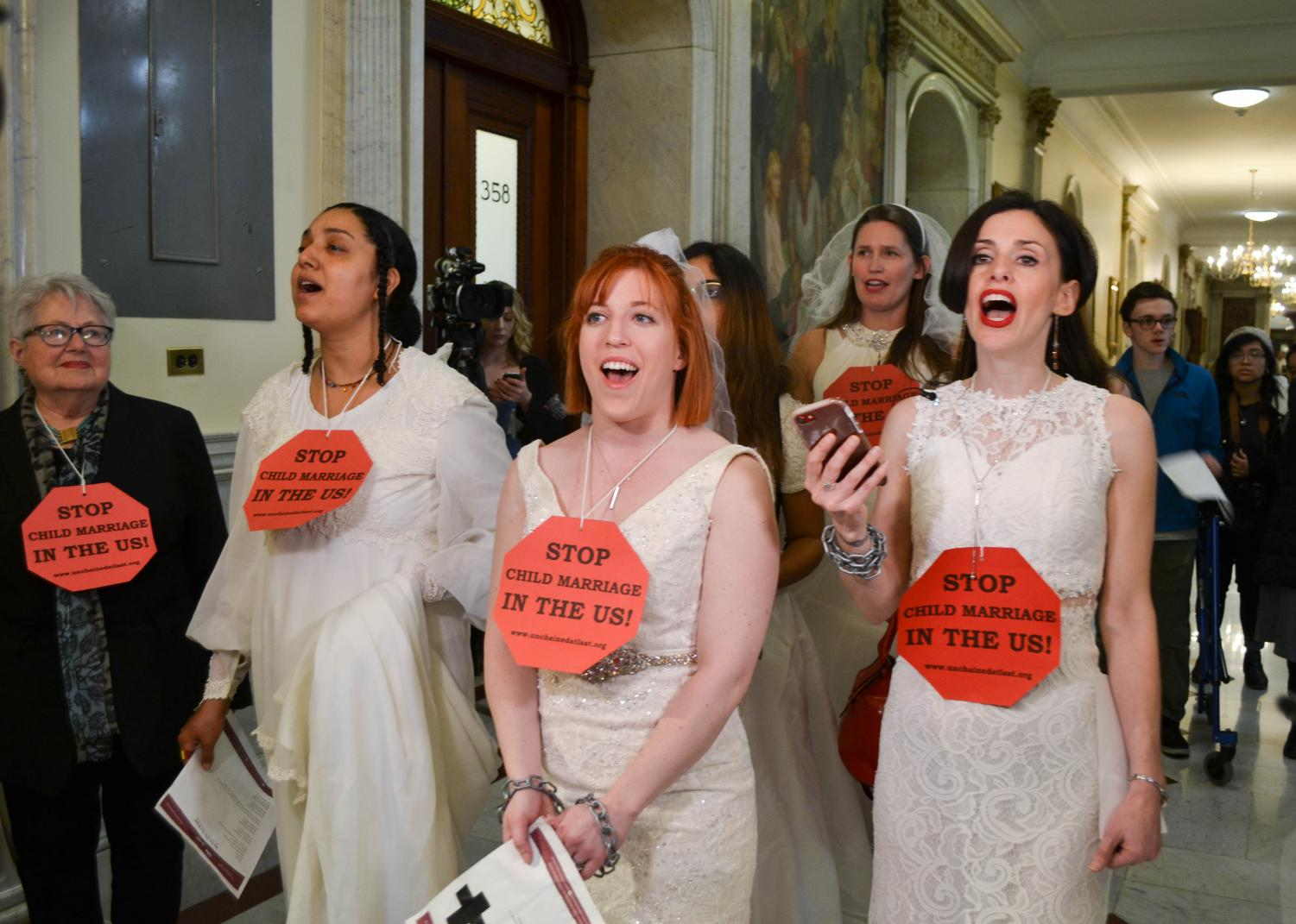 Rep. Kay Khan, Tammy Monteiro, Alex Boyer-Coffey, Amanda Parker and Fraidy Reiss sing in front of Gov. Charlie Baker's office.