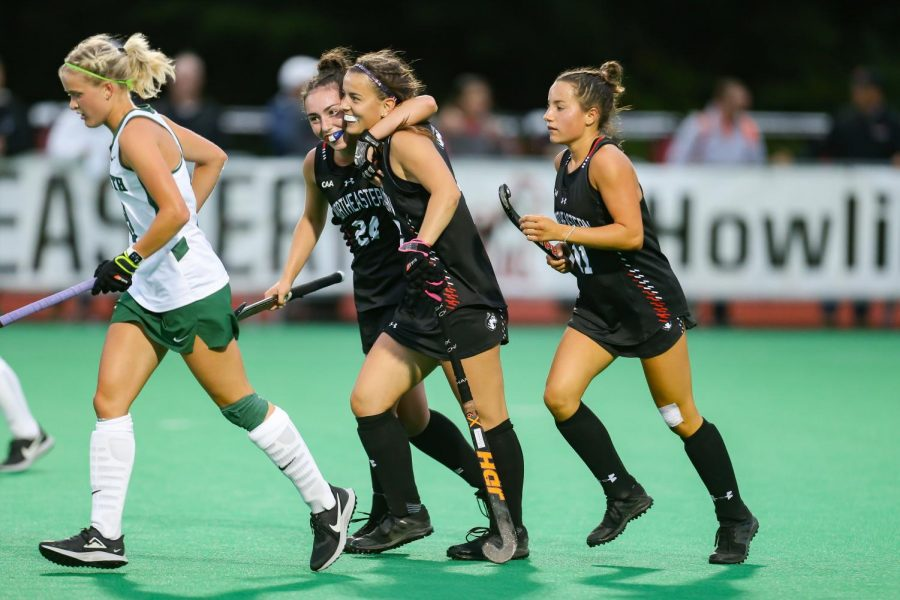 Lauren Rowe (center) and Alli Meehan (right) celebrate on the field.