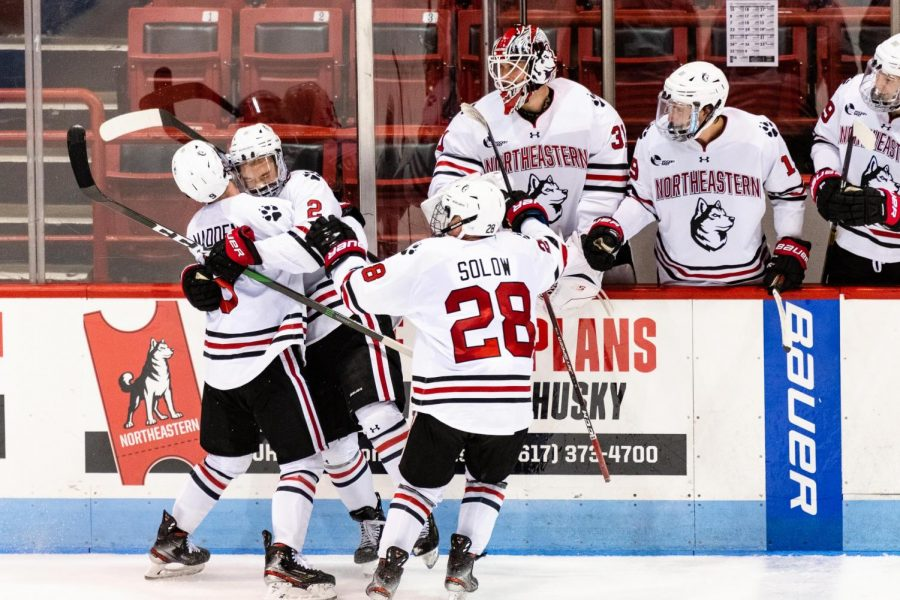 Sophomore defenseman Jordan Harris (center) celebrates with teammates Tyler Madden (left) and Zach Solow after scoring against UMass Tuesday night.