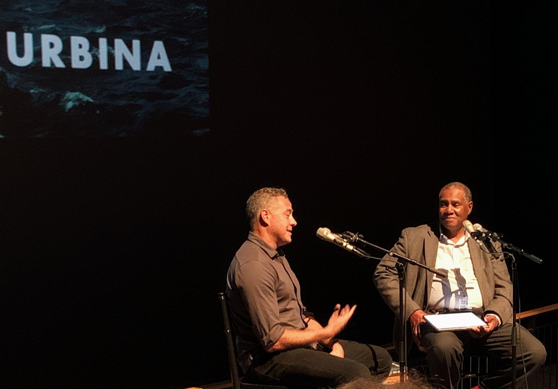 Ian Urbina, left, discusses his book