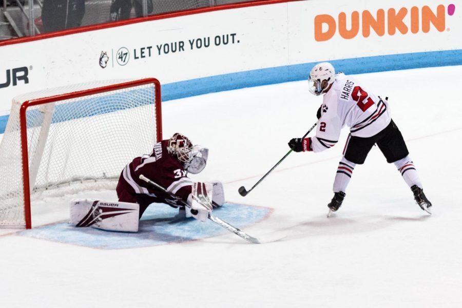Sophomore defender Jordan Harris attempts to slide the puck past the goaltender in a game against UMass last season.