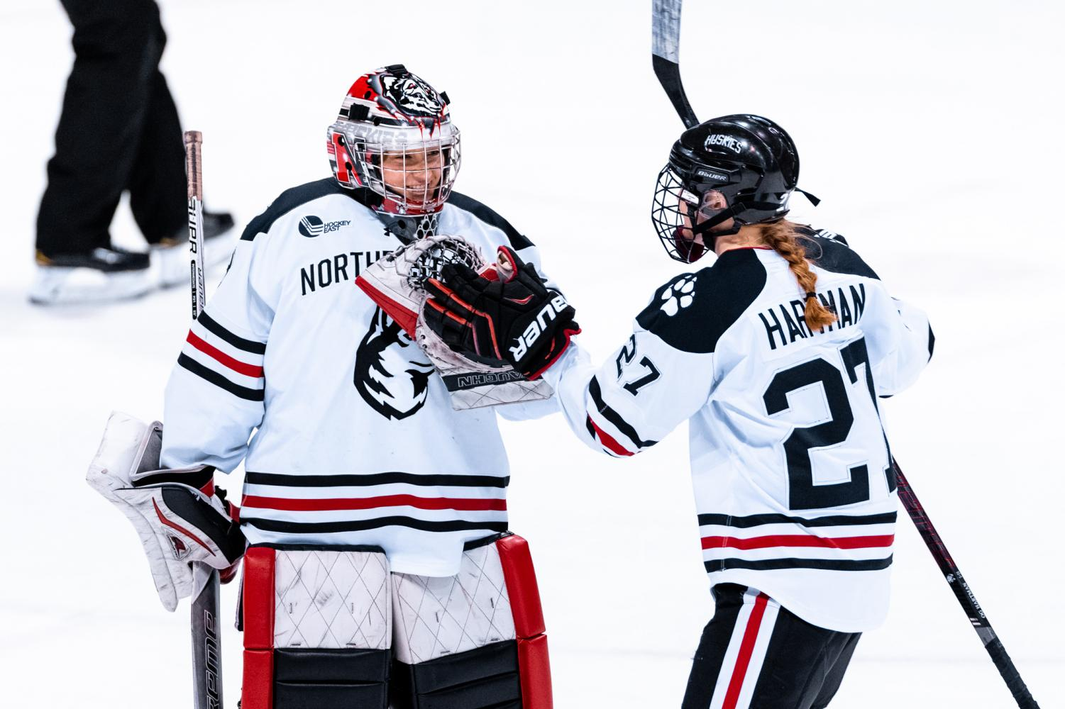 Junior goaltender Aerin Frankel and graduated defender Maddie Hartman greet each other on the ice in a match against Holy Cross last season.