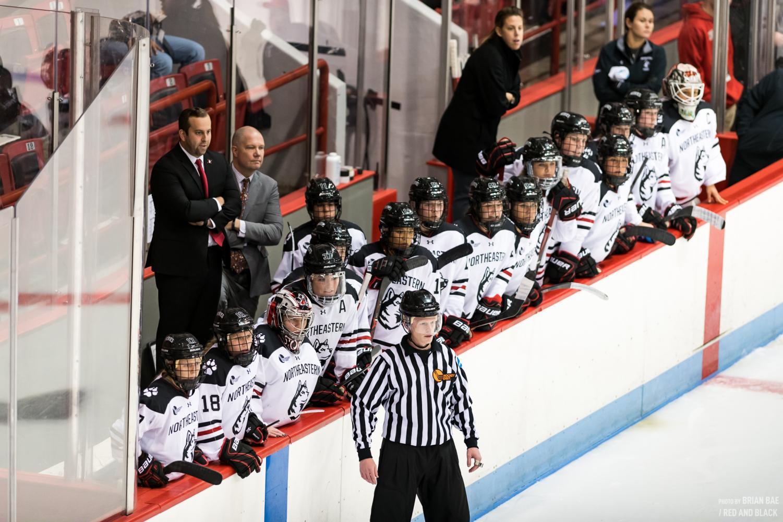 Members of the Northeastern women's hockey team watch as their teammates play a game against Colgate last season.