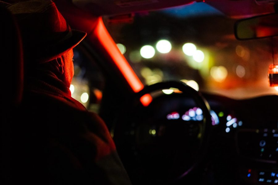 A rideshare app driver sits in his car at a red light.