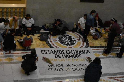 Hunger strikers line the floor of the State House with signs protesting the 15-year wait to legalize driver