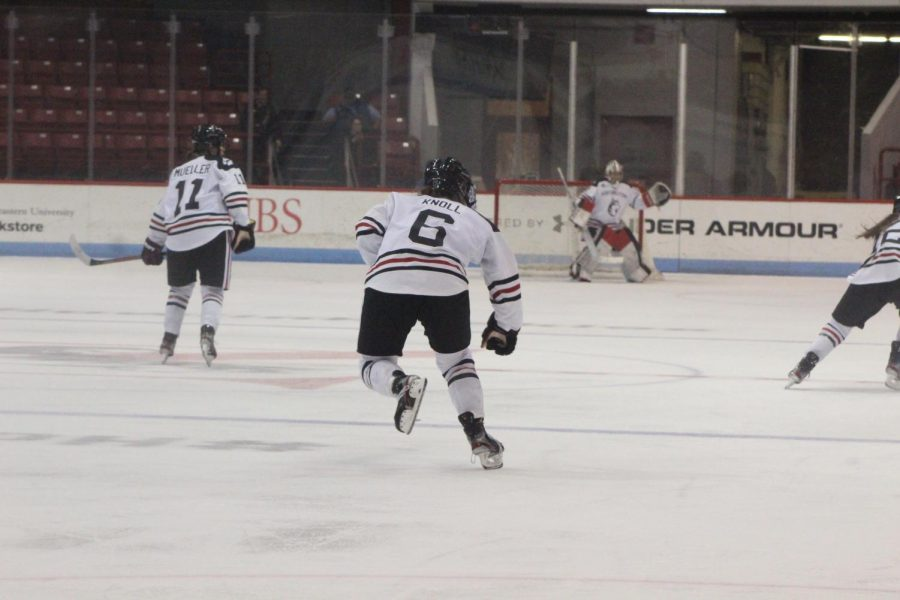 Katy Knoll, one of the Huskies' freshman stars, powers down the ice to aid Alina Mueller and Aerin Frankel on defense.