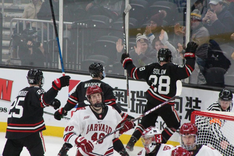 Zach Solow celebrates NU's first goal of the contest, much to Harvard's dismay.
