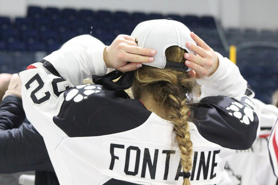 Fontaine straps on her championship hat. The junior blueliner scored three goals over championship weekend.