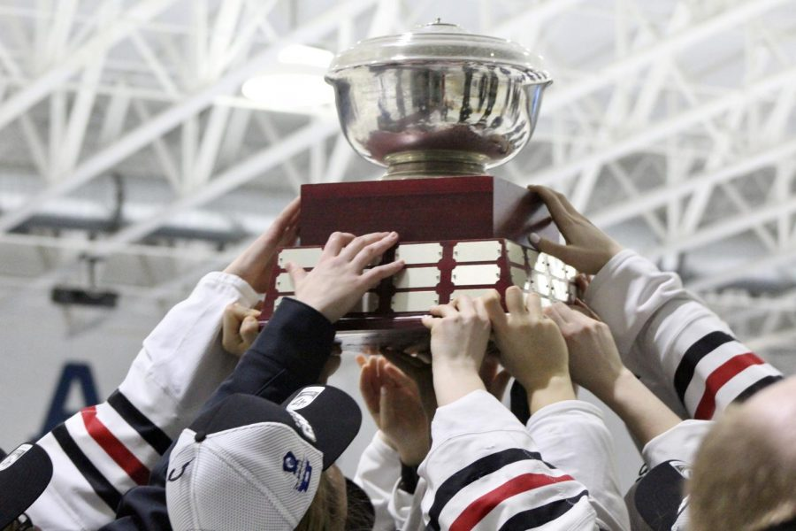 Northeastern hoists the Hockey East trophy for the third year straight.
