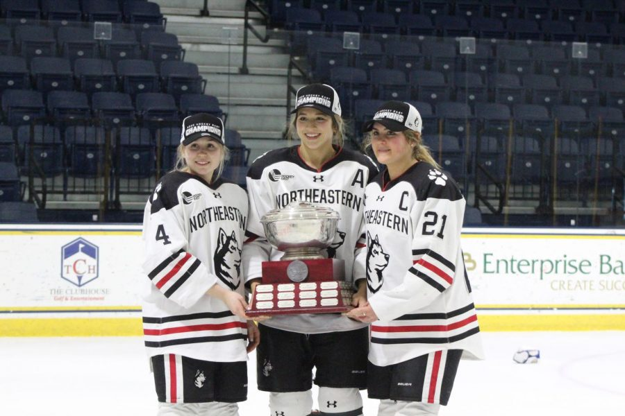 Seniors Codie Cross, Matti Hartman and Paige Capistran hold their third straight Hockey East Championship trophy.