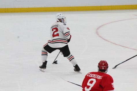 Jordan Harris handles the puck with his eye on the net during the Beanpot final.