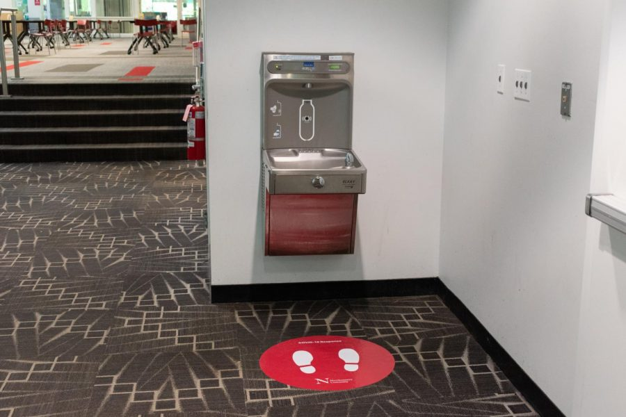 A floor decal informs users where to stand in order to properly use a drinking fountain.