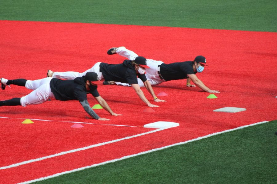 Infielders dive back to first at practice on Parsons Field.