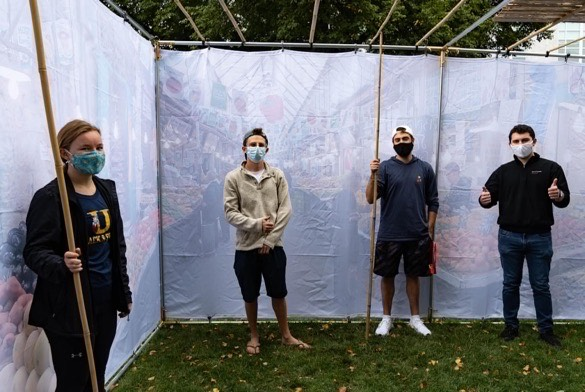 Students stand in the Sukkah built by the Alpha Epsilon Pi fraternity