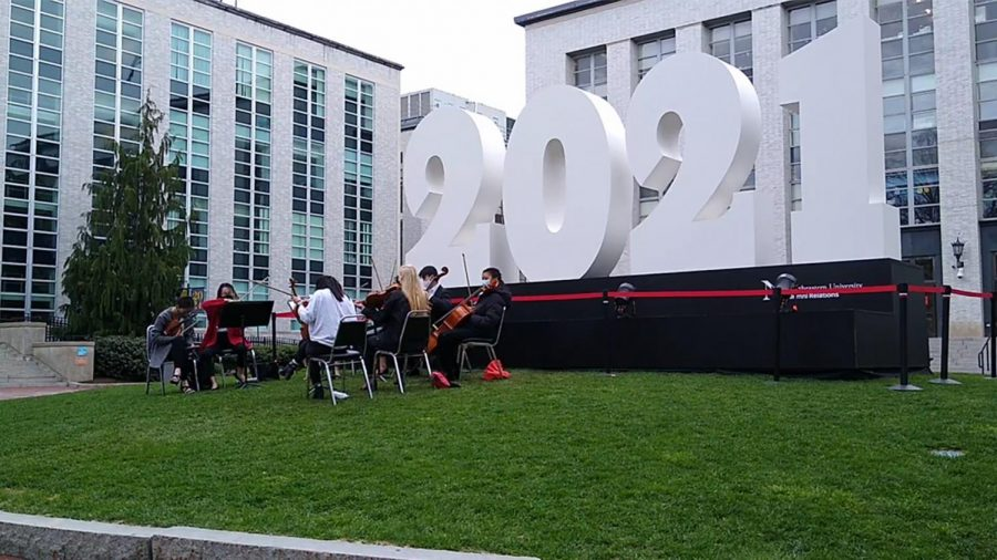 A group of classical musicians perform in front a large sculpture of the numbers 2021