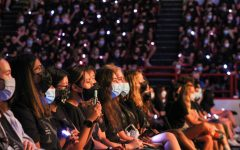 First years, wearing matching Northeastern shirts and coordinating, light-up bracelets, watch the convocation ceremony. At key moments in the ceremony, the bracelets lit up in various colors.