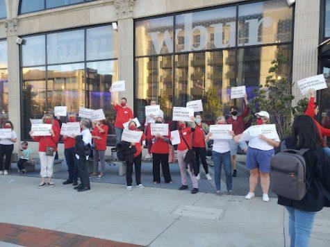 Protestors hold signs outside WBUR studio